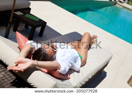 Woman lying on chaise-longue luxury pool side. Young woman enjoying summer vacation. - stock photo