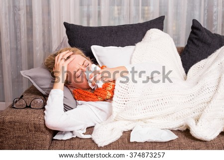 Woman lying on couch and blowing her nose