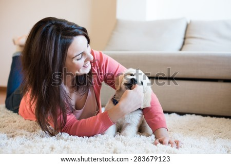 Woman lying on floor with a puppy