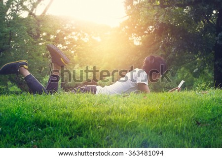 Woman lying on grass outdoor, She relax and use smartphone on sunset background - stock photo