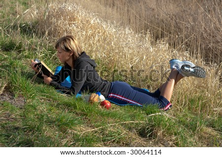 Woman lying on grass reading a book. - stock photo