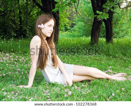 Woman lying on grass sown with flowers and holding a flower - stock photo