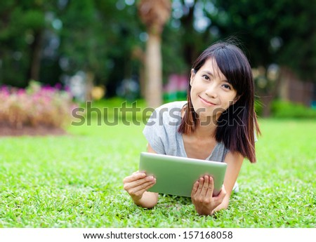 Woman lying on grass with tablet computer