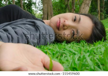 Woman lying on green grass - stock photo