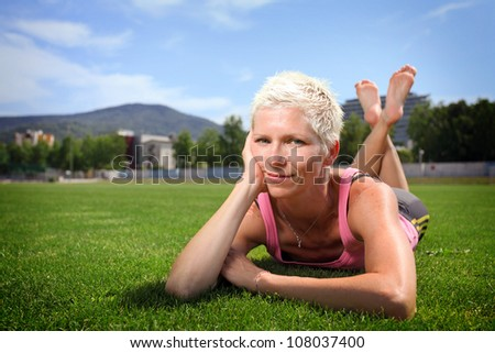 Woman lying on green grass after jogging - stock photo