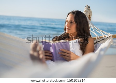 Woman lying on hammock holding book and thinking on the beach - stock photo