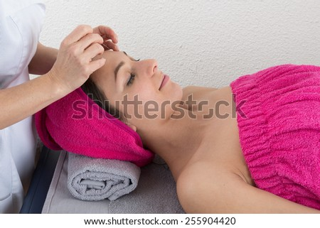 Woman lying on massage table getting acupuncture - stock photo