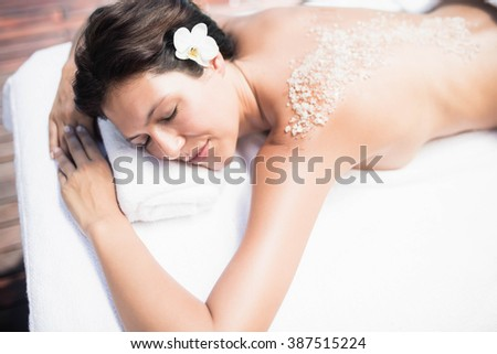 Woman lying on massage table with salt scrub on back in a spa - stock photo