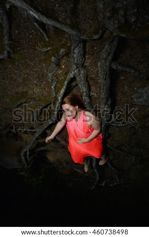 Woman lying on roots of tree