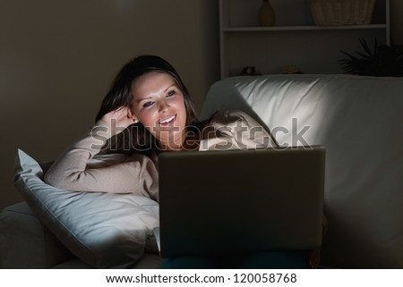Woman lying on sofa with her laptop in night in the living room - stock photo