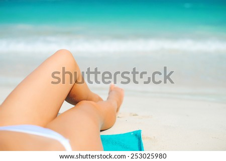 Woman lying on the beach. Legs. - stock photo