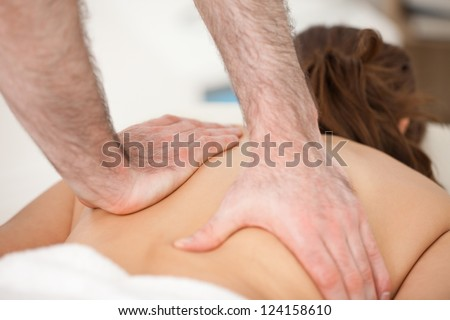 Woman lying on the belly while being massaging with two hands of doctor indoors - stock photo
