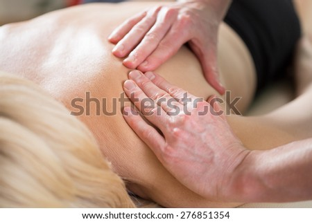 Woman lying on treatment couch and having shoulder massage