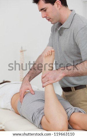 Woman lying while a physiotherapist is bending her leg in a room - stock photo