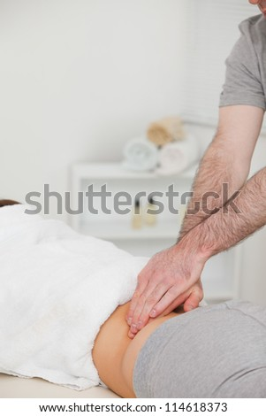 Woman lying while a physiotherapist is massaging her back in a physio room
