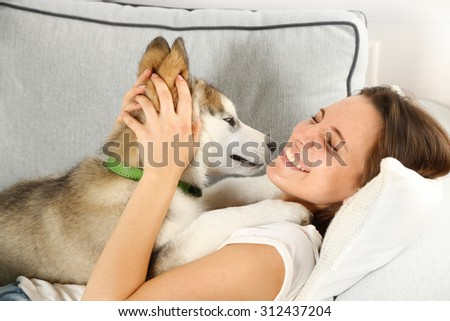 Woman lying with her malamute dog on sofa in room