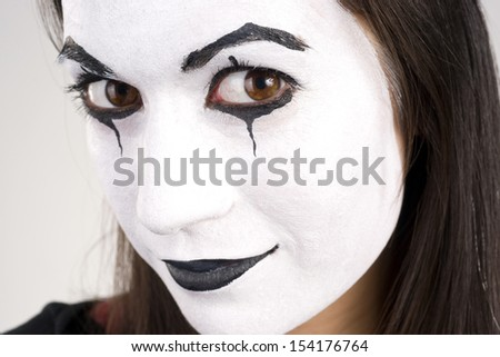 Woman made up in white face looks right into the camera