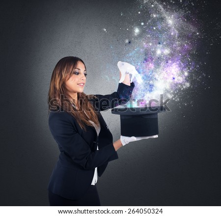 Woman magician makes magic with her hat - stock photo