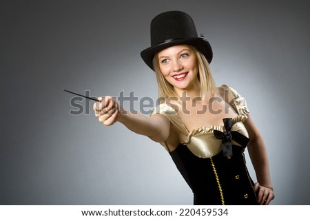 Woman magician with magic wand and hat - stock photo