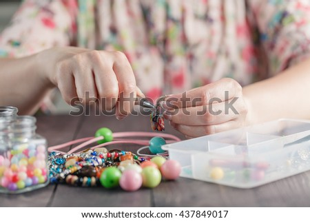 Woman make handmade jewellery. Leisure concept