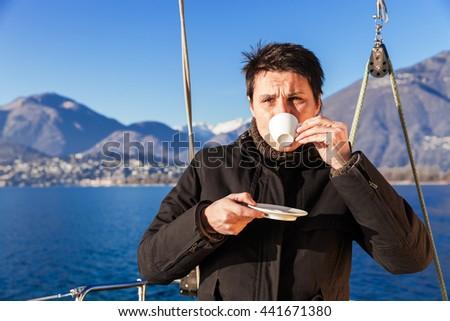 woman makes a coffee break aboard his sailboat - stock photo