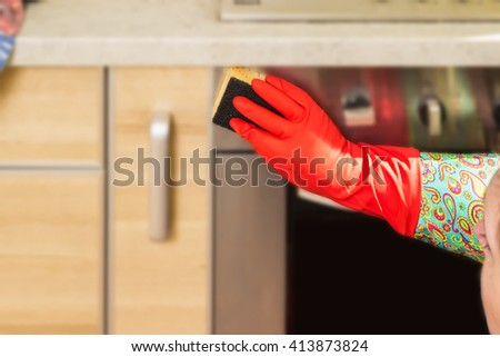 Woman makes chores in the kitchen at home, cleaning in gloves with a sponge. Cropped view. cleaning service - stock photo