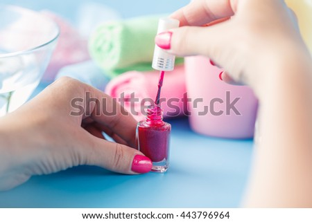 Woman makes herself manicure, on white background