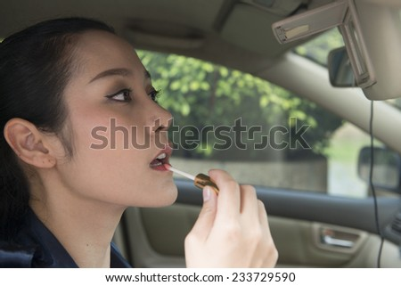 woman makeup in the car  - stock photo