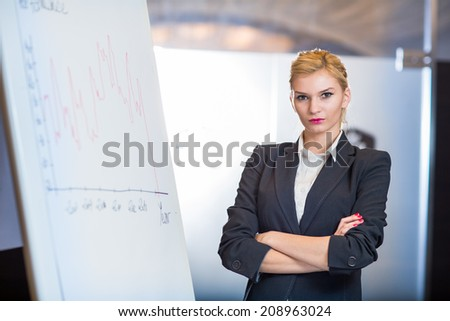 Woman making a business presentation - business success growth chart. Business woman drawing graph showing profit growth on whiteboard - stock photo