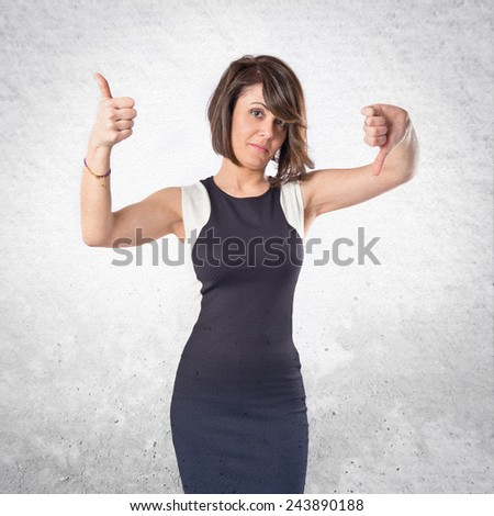 Woman making a good and bad signs over textured background  - stock photo