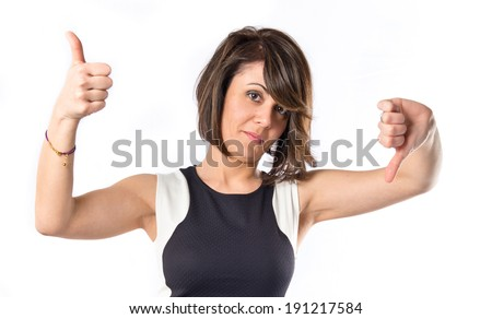 Woman making a good and bad signs over white background  - stock photo