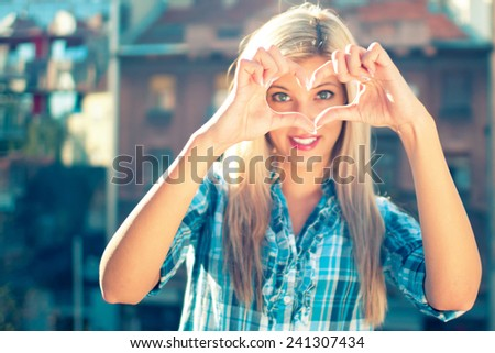 Woman making a heart gesture with her hands framing her eyes - stock photo