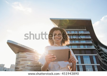 Woman making a video call via computer tablet in a big city.
