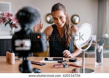 Woman making a video for her blog on cosmetics. Smiling young lady facing a recording camera with various cosmetic items on table.