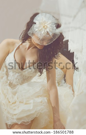 Woman making adjustment to wedding gown in professional fashion designer studio - stock photo