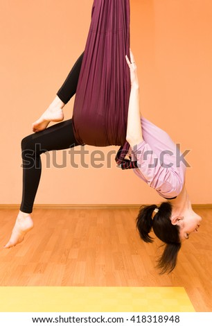 Woman making aerial yoga exercises, indoor, fly yoga - stock photo