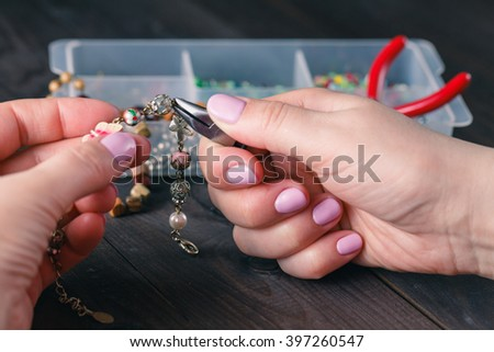 Woman making beads. Box with beads, spool of thread, plier and glass hearts to create hand made jewelry on old wooden background