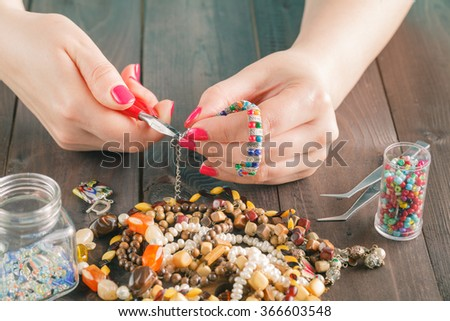 Woman making bears on rustic wooden table - stock photo