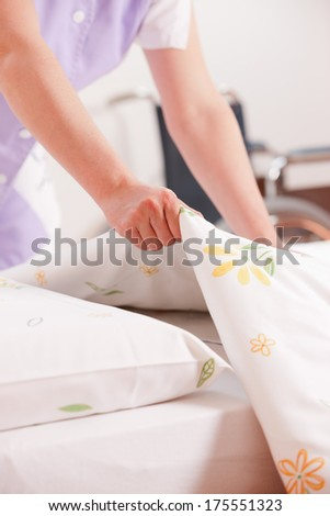 Woman making bed and changing bedding in guest room.