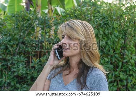 Woman Making Call In Backyard Garden