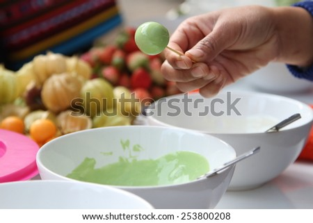 Woman making cape gooseberry in green tea chocolate glaze. - stock photo