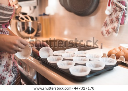 Woman making cupcakes in baking tray closeup in kitchen