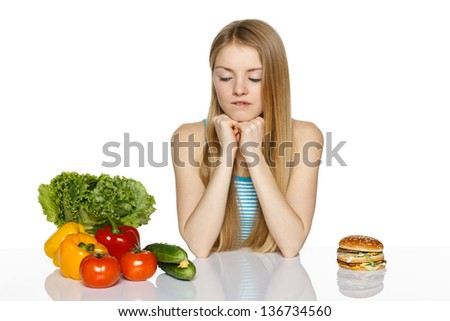 Woman making decision between healthy food and fast food, over white background - stock photo