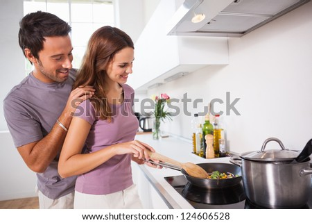 Woman making dinner with partner watching in kitchen - stock photo