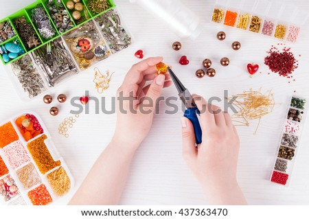 Woman making handmade jewellery. Boxes with beads, glass hearts, accessories for needlework on white wooden table. Handmade accessories. Top view - stock photo