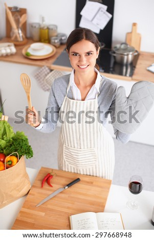Woman making healthy food standing smiling in kitchen - stock photo