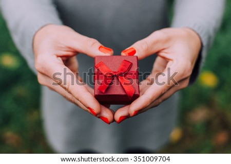 Woman making heart with gift and hands - stock photo
