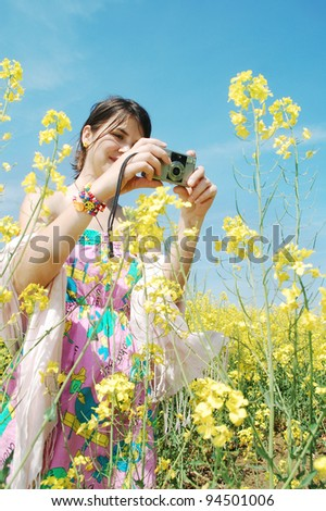 woman making photos at a rapeseed flower - stock photo