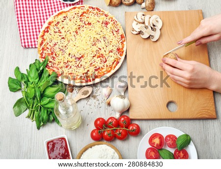 Woman making pizza on table close up - stock photo