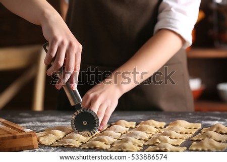Woman making ravioli on table